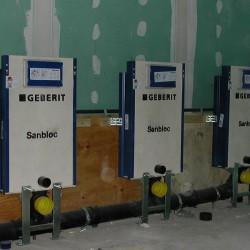 Toilettes d'entreprise - installation des chasses d'eau dans la cloison